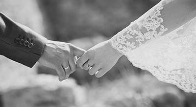 Close up of a man in a suit and woman in a wedding dress holding hands (black and white)