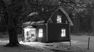 Countryside cottage on a winter evening, lights on, with a bare tree in the foreground and a dark forest in the background (black and white)