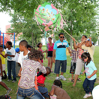 Children and adults of different cultures celebrate a birthday around a piñata.