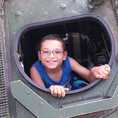 A smiling child coming out of a military tank's hatch.