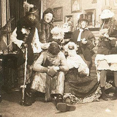 Six people in disguises and masks for the Mardi Gras festivities. They are gathered in a living room.