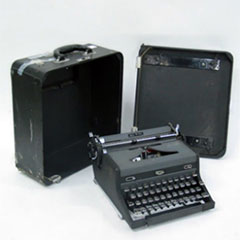A typewriter and its carrying case.