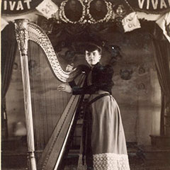 A young woman, Nellie Madigan, poses next to a harp.