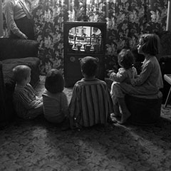 Children sitting in front of a TV set.