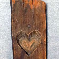Wooden sugar mould made around 1900. A heart is carved in the centre of a wooden board.