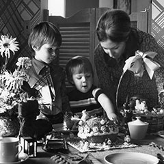A mother and her two children are looking at a cake and some Easter chocolates, including a chocolate bunny. We can also see a table set with a bouquet of flowers.