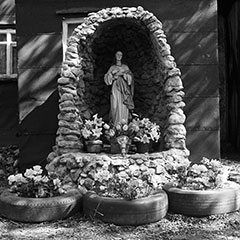 A stone Marian niche intended for the Virgin Mary is found in front of a house. Flowers are placed near the statue.