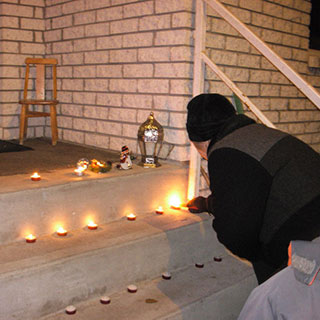 A man lights candles placed on the steps in front of a house.