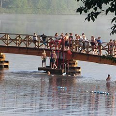 Children playing on a bridge to which a ladder is attached, allowing them to swim in the lake.