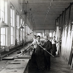 A man dressed in a suit explains to a worker how to cut a long pipe. In the background, there are two men working.