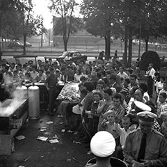 People are gathered for a corn roast in a park. A boiling tank of water can be seen.