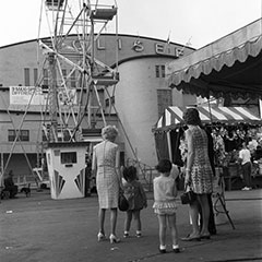 Two mothers and their young daughters stand before the Ferris wheel and a game booth. In the background, we can see the Québec Coliseum.