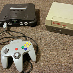 On the left, the Nintendo 64 and its controller. On the right, the NES, the first Nintendo game console.