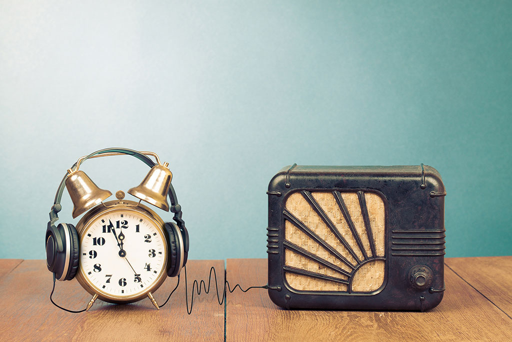 Alarm clock, headphone and radio receiver on table