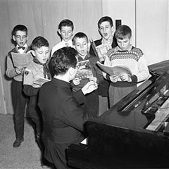 A small group of children is rehearsing choral singing with Father Claude Thompson who is sitting at the piano.