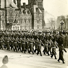 Soldiers from the Royal 22nd Regiment march in front of the Parliament building in Ottawa. A crowd watches them. In the foreground, we can see a man running.