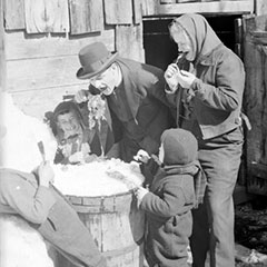 A man and woman with three children tasting maple taffy on snow in front of a wooden house.