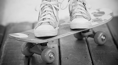 Feet in sneakers on a skateboard situated on a wooden balcony (black and white)