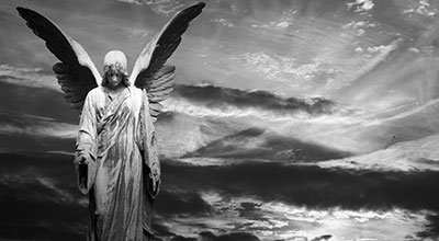 Statue of an angel with spreading wings with a sunset in the background (black and white)