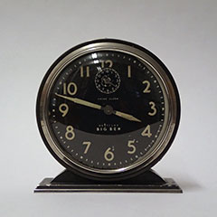 Round and black Big Ben alarm clock.