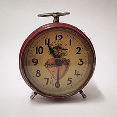 Alarm clock with a painted Sacred Heart motif behind the hands.