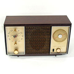 Wood and metal clock radio with a clock face, a frequency tuner and a speaker.