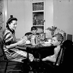 A mother and her sons are having breakfast. On the table, there is a toaster, a cereal box and a coffee maker.
