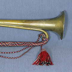 Bugle adorned with red, black and beige braided threads.