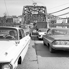 Traffic jam on an iron bridge where a dozen cars are stalled. In the background, we can see a city.