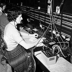 A woman works as a telephone operator in front of a control panel. She is wearing a headset and microphone.