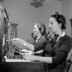 Two women working as telephone operators. They wear a headset and a microphone allowing them to hear and speak. We can see in front of them the switchboard used for telephone communications.