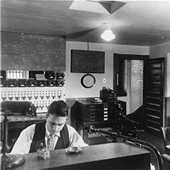 Two men are at the controls of the Shawinigan Water and Power Plant. We can see a communication system in front of them and different control panels in the background.
