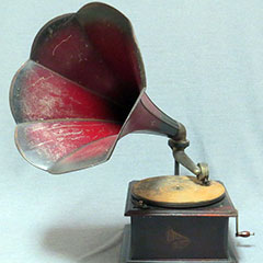 Gramophone of the Columbia Gramophone Company Limited made of wood and metal. The horn is red.