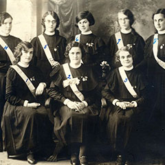 Photograph of a ribbon presentation ceremony. Seven young women pose proudly with their gowns and ribbons.
