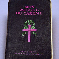 Black cover of a Lent missal on which there is a pink cross topped by a green laurel wreath.