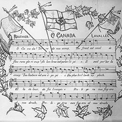Handwritten music score of the Canadian National Anthem. Three flags and maple leaves are drawn around the score.