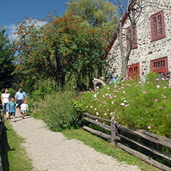 A family of two adults and two children is walking the trail leading to the Moulin seigneurial de Pointe-du-Lac.