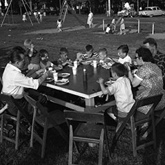 In the foreground, we can see two couples and their children eating a picnic lunch on a table. In the background, kids play in the structures of a children's park.