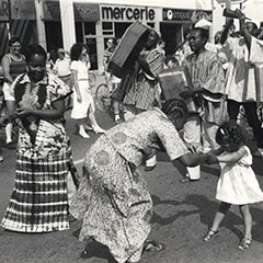 A woman and a little girl are dancing. Next to them, another woman is also dancing. Men are playing music with instruments.