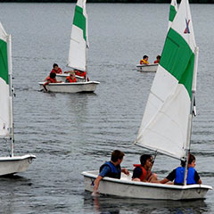 Children playing on small sailboats.