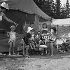 Two mothers and some children are sitting in front of camping tents. They are dressed in their bathing suits.