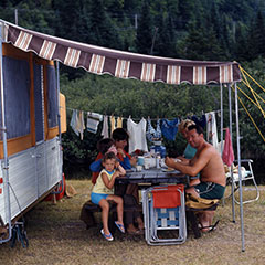 A family is eating on a picnic table under the shade of a folding camping trailer.
