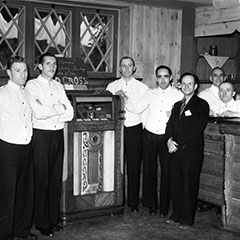 Some waiters and Mr. Louis Faust stand near the Wurlitzer jukebox in Sainte-Adèle hotel.