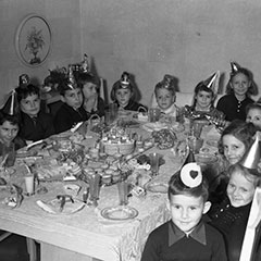 Children are gathered around a table decorated for a birthday party. They are wearing cardboard party hats.