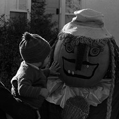 A mother holds her child in her arms in front of a scarecrow that has a decorated pumpkin with a grimacing face for a head.