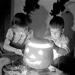 Two children are posing with a carved pumpkin. The girl is holding a spoon while the boy is putting the lid back on top.