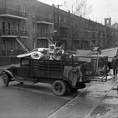 Moving scene where a truck is loaded with furniture, mattresses and chairs. A man is standing on the load.