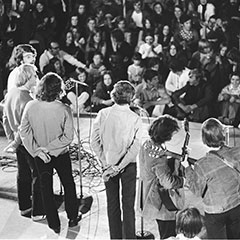 Seven musicians and singers perform on a stage in front of a crowd sitting on the ground.